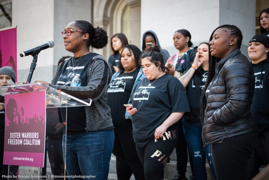 A young Black woman with glasses wearing a jacket and jeans speaks at a podium with 9 young women standing behind her