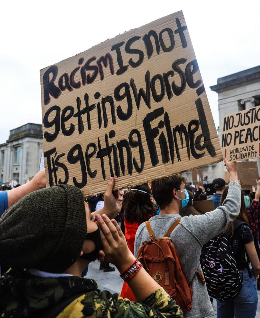SIgn that says racism isn't getting worse, it's being filmed